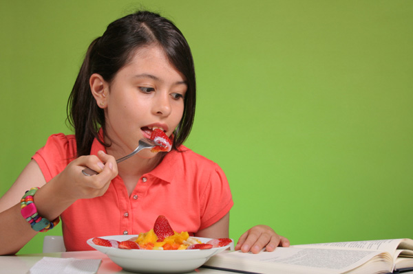 Girl studying and eating fruit