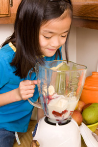 Little girl making smoothie