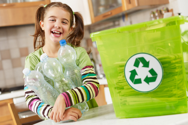 Little girl recycling in kitchen