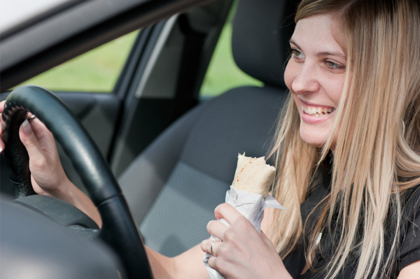 Woman eating wrap in car
