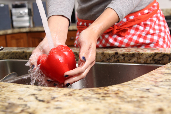 Woman washing red peppers