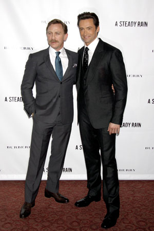 Daniel Craig with a mustache, next to Hugh Jackman