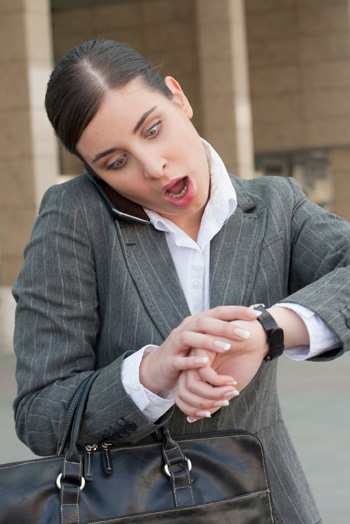 Late business woman checking watch