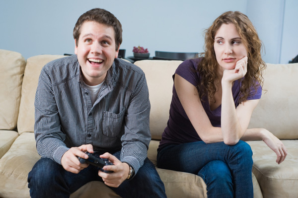 Unhappy girlfriend watches boyfriend play video games