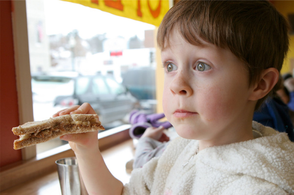 Boy eating sandwich on whole wheat
