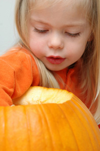 Girl removing pumpkin guts