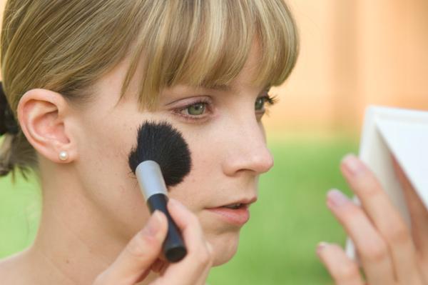 Woman with green eyes applying blush