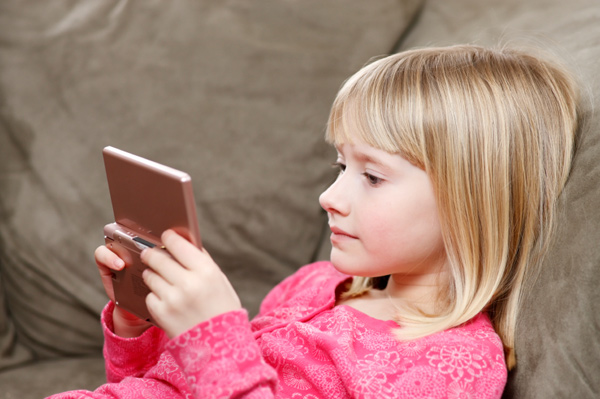 Little girl playing with handheld video game