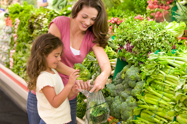 Mom and daughter shopping for broccoli