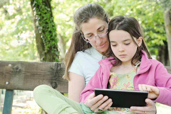 Mom homeschooling daughter with e-reader