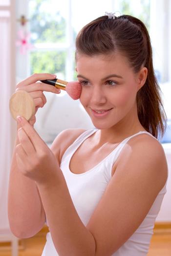 Teen girl applying blush