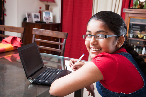 Tween girl doing homework in living room on laptop