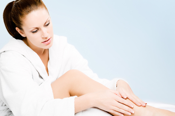 Woman moisturizing legs with lotion