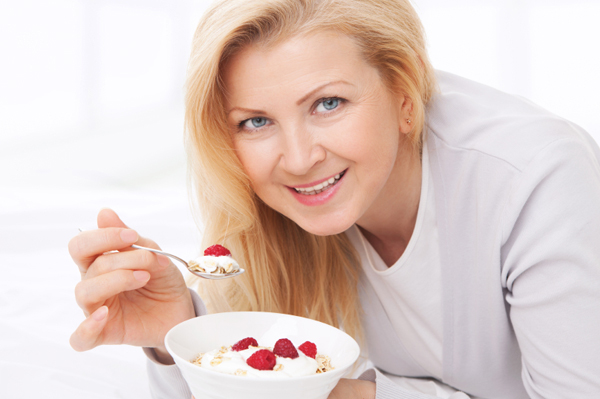 Woman eating berries with flax and yogurt