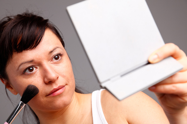 Woman with black hair applying blush