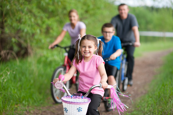 Girl riding bike with family