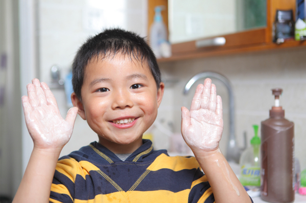 Little boy washing hands at home