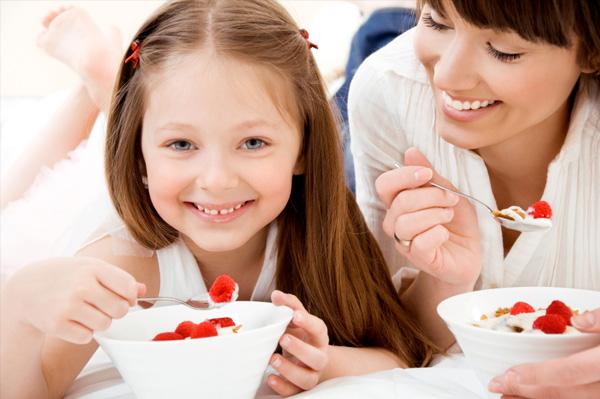 Mom and daughter eating yogurt