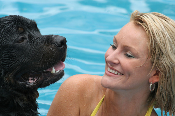 Woman in pool with dog