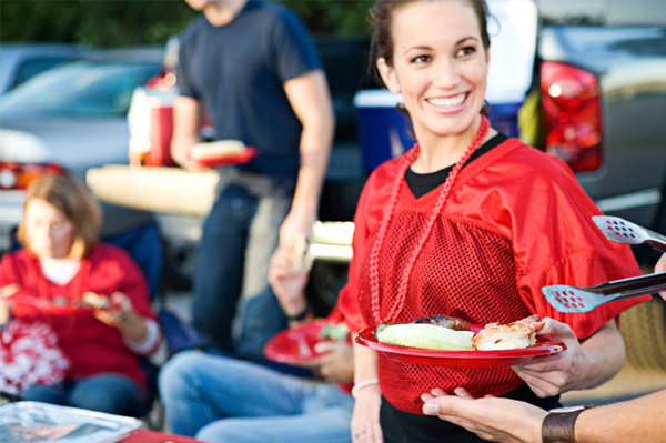 Woman getting hamburger from tailgate