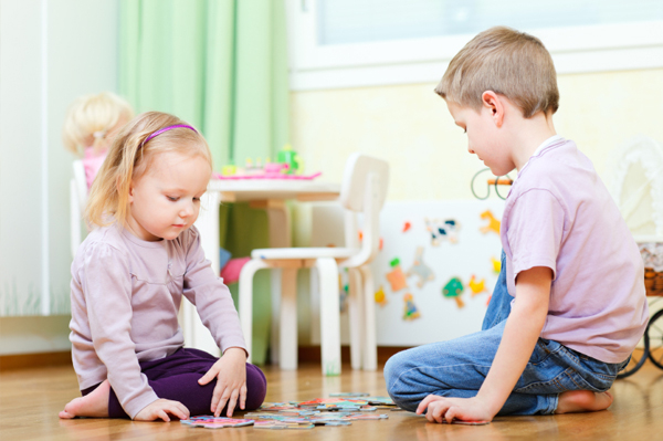 Brother and sister playing with a puzzle