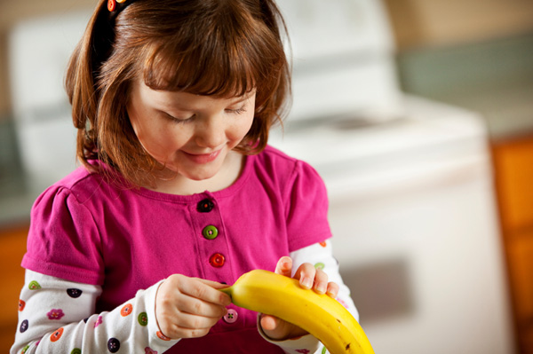 Girl peeling banana