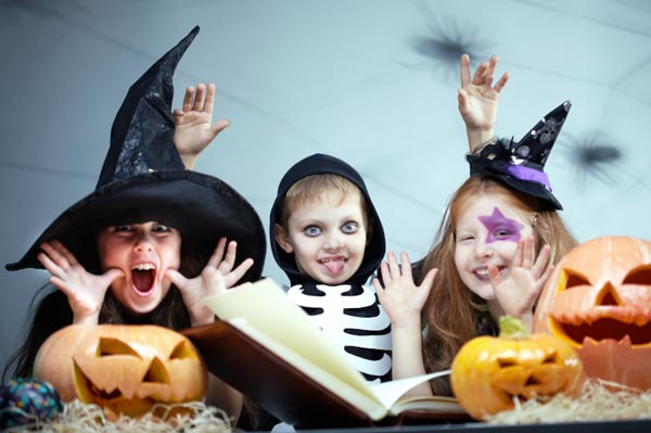 Costumed kids reading a Halloween book