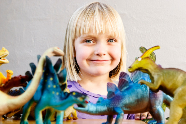 Little girl playing with toy dinosaurs