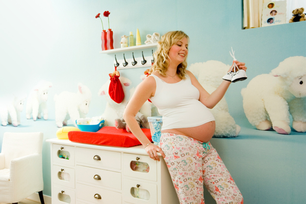 pregnant-woman-holding-baby-shoes