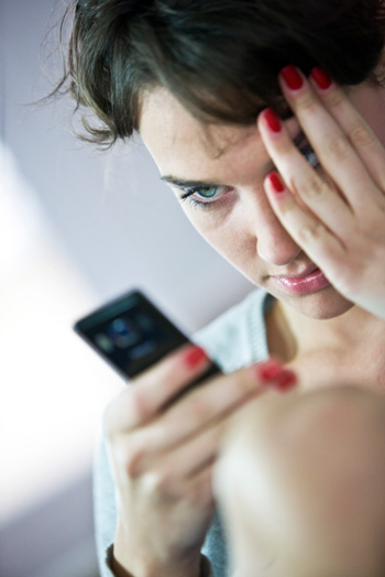 Upset woman reading text message