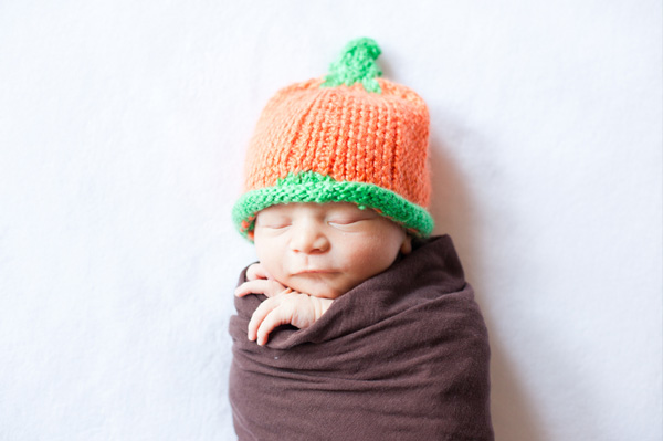 Infant wearing pumpkin hat