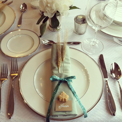 Classical cottage with solid staples, like gold rimmed plates, solid napkins and a simple place card