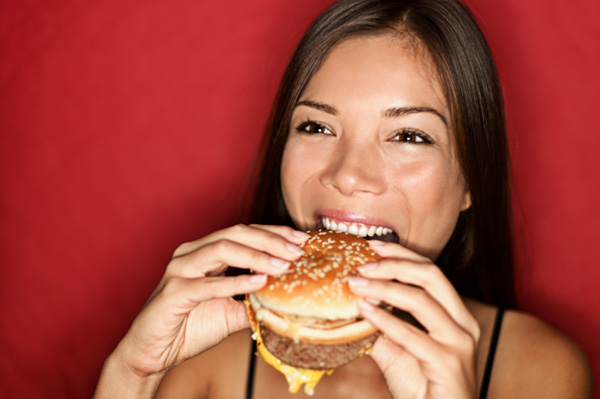 Woman eating a fast food sandwich