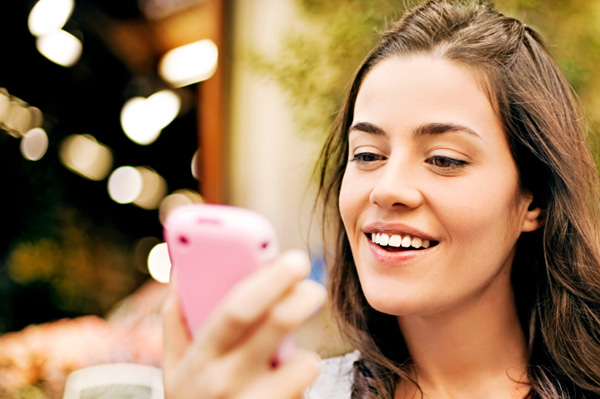 Woman looking at pink cell phone