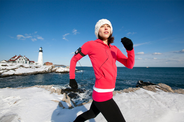 Woman running along coast in winter