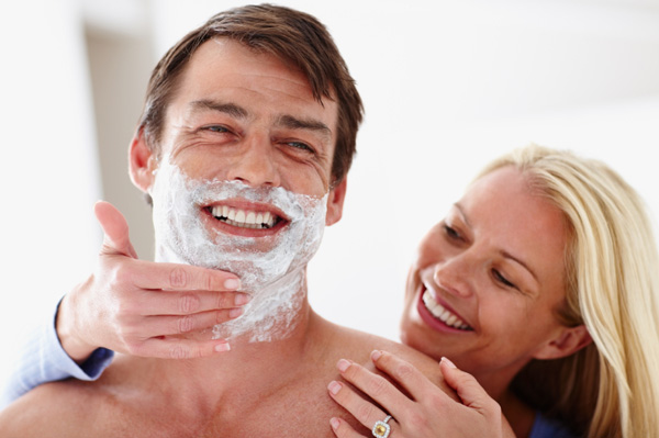 Woman shaving her husband's face