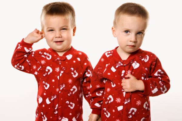 Twin brothers in matching Christmas pajamas