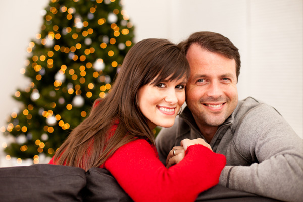 Couple holding hands in front of Christmas tree