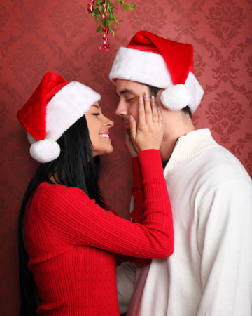Couple kissing under mistletoe in bedroom