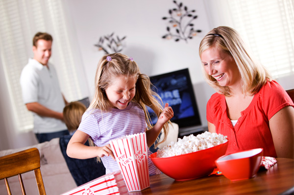 Family laughing in living room watching movie