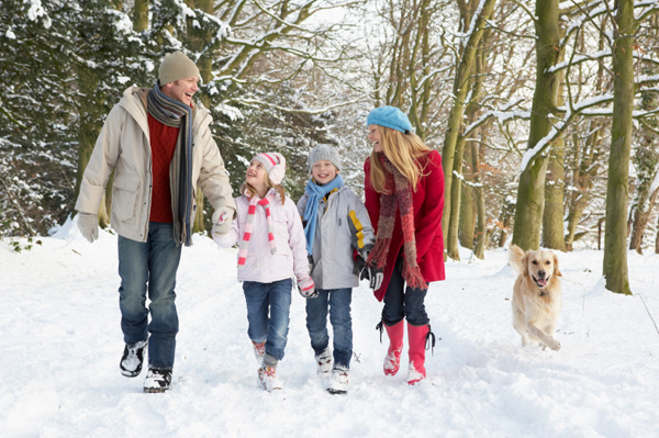 Family walking dog in the snow