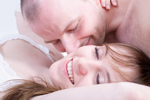 Happy couple in bed having sex