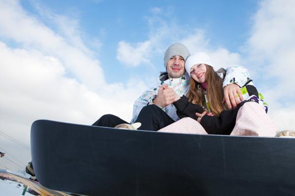 Happy couple snowboarding