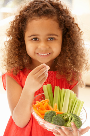 Little girl eating vegetables