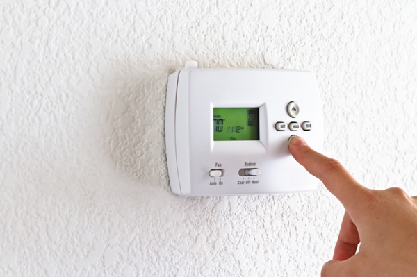 Woman turning down thermostat