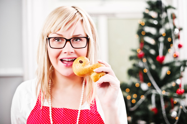 Woman eating pastry in front of Christmas tree