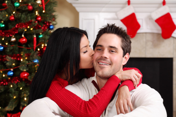 Woman kissing husband under Christmas tree