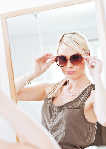 Woman putting on sunglasses