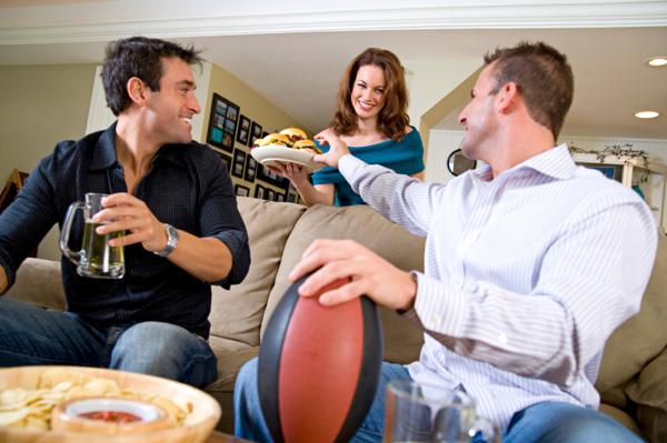 Woman serving hamburgers to husband and friend watching football