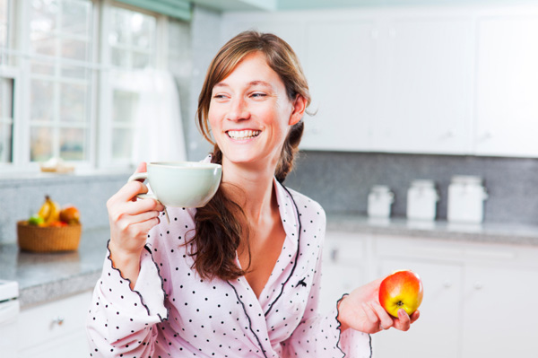 Woman starting day with apple